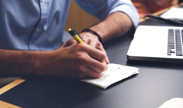 man taking notes and laptop